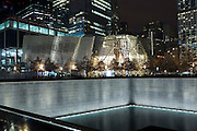 One World Trade Center complex site with museum and illuminated 9/11 Memorial North Pool in New York, USA