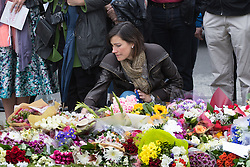 Parliament Square, Westminster, London, June 17th 2016. Following the murder of Jo Cox MP friends and members of the public lay flowers, light candles and leave notes of condolence and love in Parliament Square, opposite the House of Commons. PICTURED: A woman looks at the floral triputes and notes in Parliament Square.