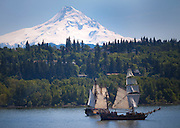 Boats simulate a Pirate battle in the Columbia River near Hood River, Oregon and White Salmon, Washington.  Mt Hood is seen in the background.