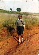 A girl walks home from school in the open fields of Kibera.