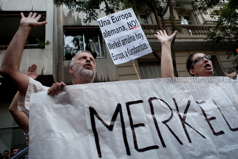 Protesters shout and hold a placards during a demonstration against German Chancellor Angela Merkel's official visit to Spain, in central Madrid on September 6, 2012. Placards reads 'Non to a German Europa. Merkel is bankrupting Europe with Eurobombs'. Merkel is in Spain for talks with conservative Spanish President Mariano Rajoy.