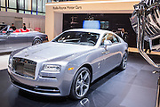 "New York, NY - 1 April 2015. A Rolls Royce Wraith in the ""Inspired by Film"" package, which harkens back to the golden age of film. A prop movie light can be seen at the right of the frame, and the vehicle sports doors hinged at the rear, called by Rolls ""coach doors,"" but popularly referred to as ""suicide doors."""
