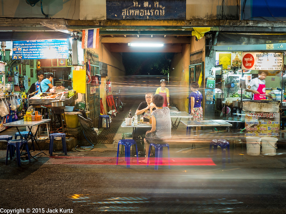 26 MAY 2015 - BANGKOK, THAILAND: Lights from a passing motorcycle streak through the photo while people eat at street food stalls on Sukhumvit Soi 38 in Bangkok, one of the most famous street food locations in the Thai capital. The food carts and small restaurants along the street have been popular with tourists and Thais alike for more than 40 years. The family that owns the land along the soi recently decided to sell to a condominium developer and not renew the restaurant owners' leases. More than 40 restaurants and food carts will have to close. The first wave of closings could start as soon June 21 and all of the restaurants are supposed to close over the next several months.     PHOTO BY JACK KURTZ