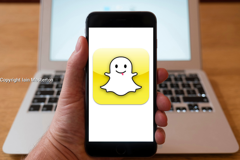 Using iPhone smartphone to display logo of Snapchat social media site