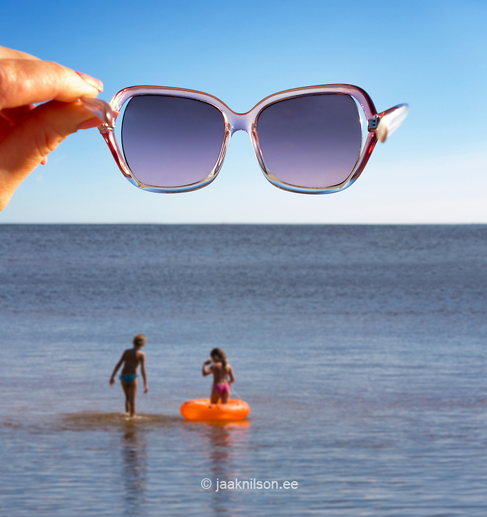 Woman hand holding sunglasses in air over water. Kids in water with inflatable life ring. Horizon.