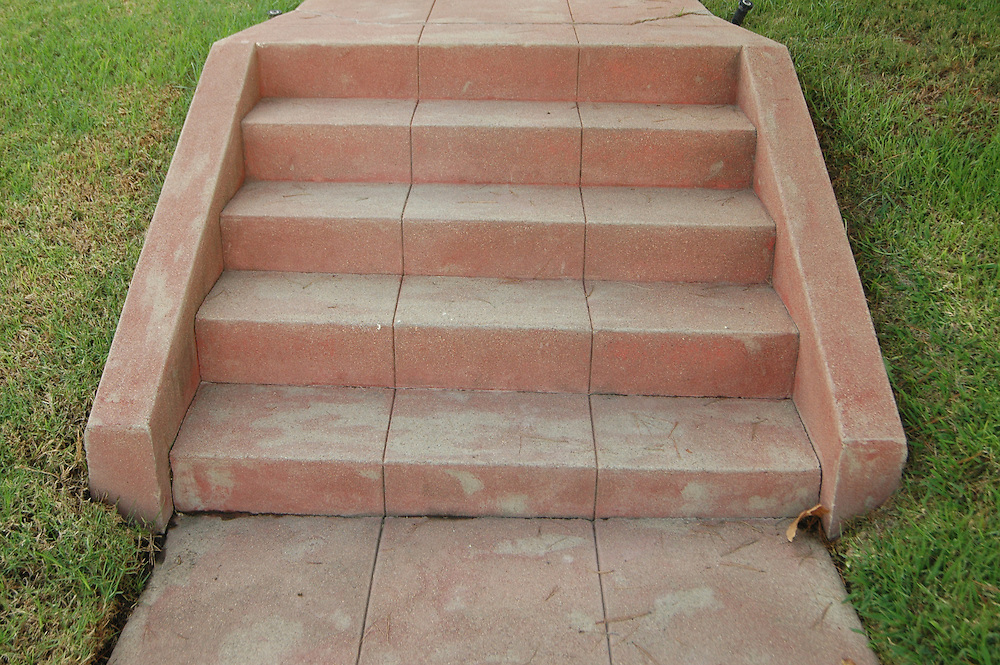 Old red-concrete steps, 1930's era, leading up a grassy slope.