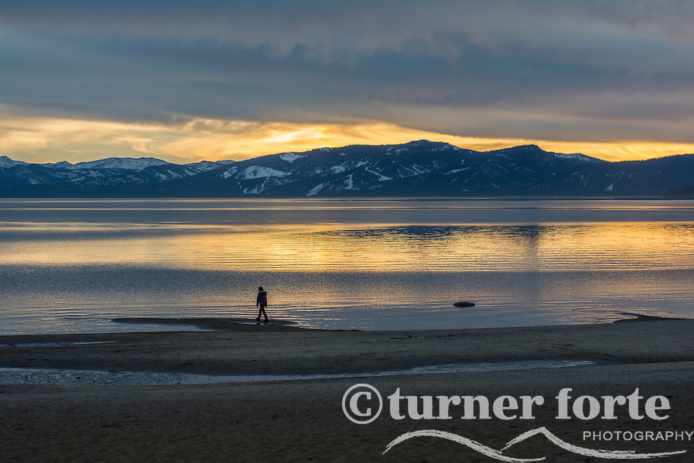 Adult walks out onto a sliver of sand at sunset in winter on Kings Beach, Lake Tahoe, California.