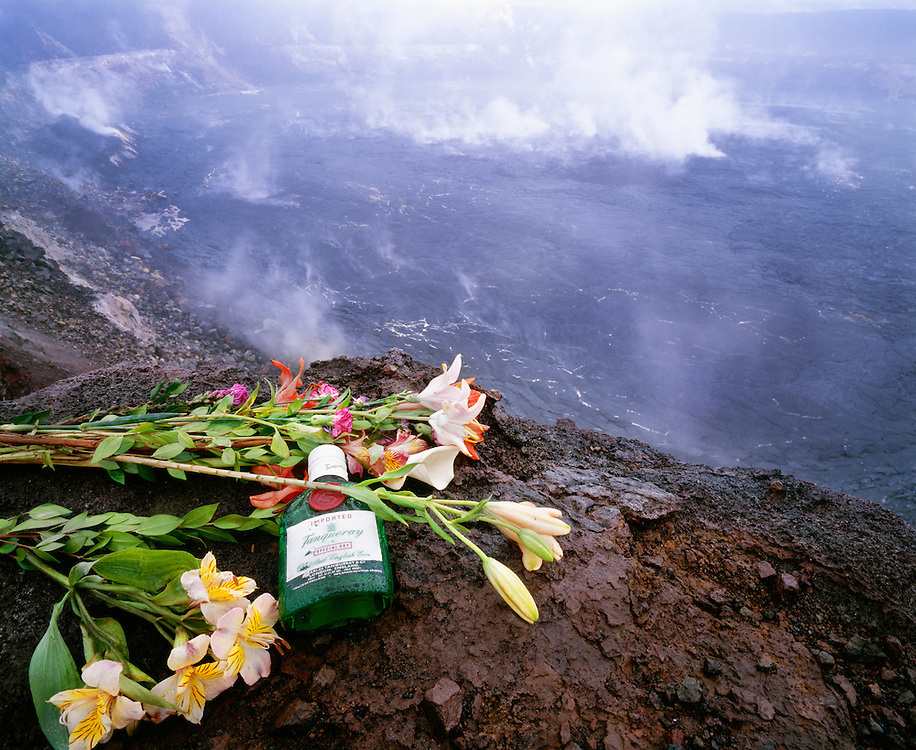 0801-1005B ~ Copyright: George H.H. Huey ~ A traditional offering of flowers and gin for Pele, the goddess of Hawaii's volcanoes.  Halema'uma'u Crater in background.  Kilauea Caldera.  Hawaii Volcanoes National Park,  The Big Island, Hawaii.