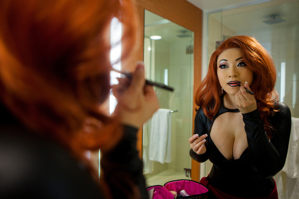 Cosplayer Yaya Han puts on lip liner in preparation for portraying Phoenix from Marvel Avengers Alliance.