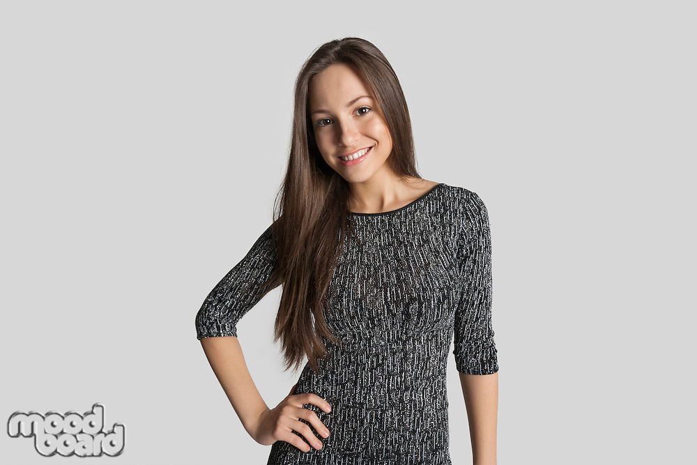 Portrait of smiling girl in dress standing against gray background