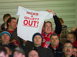 "LIVERPOOL, ENGLAND - Sunday, March 28, 2010: A Liverpool supporter in the Main Stand displays a T-Shirt reading ""HICKS & GILLETT OUT!"" in protest at the club's American owners before the Premiership match against Sunderland at Anfield. (Photo by: David Rawcliffe/Propaganda)"