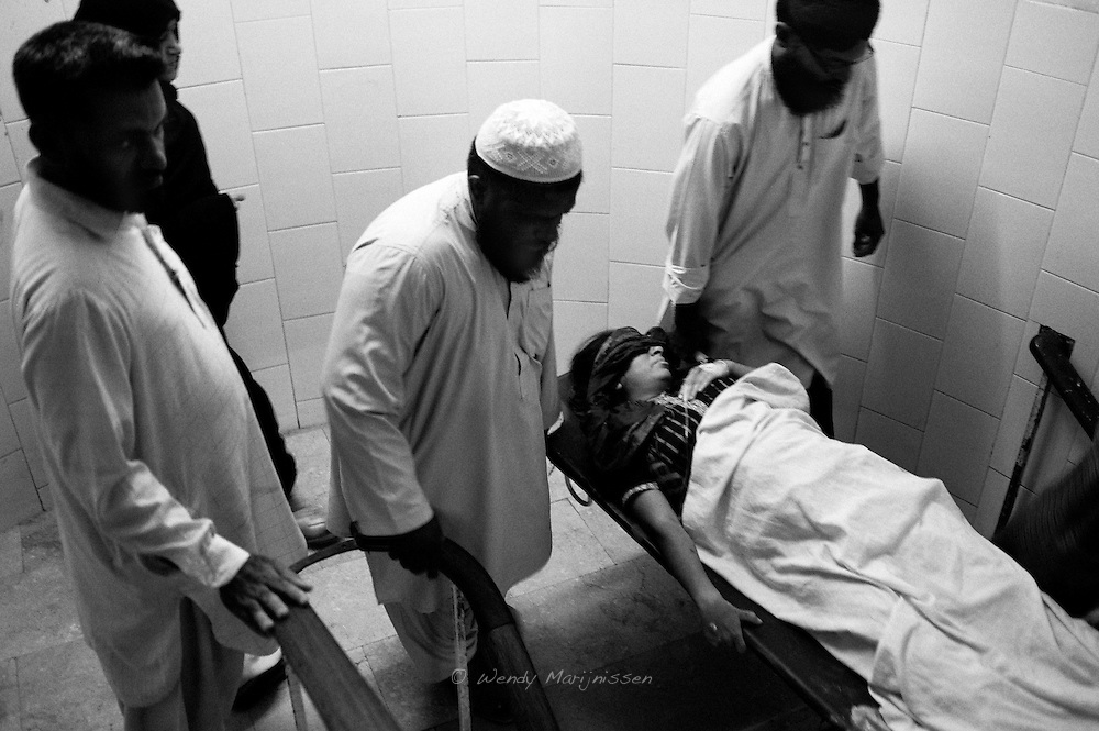 Family members and hospital staff carry Nafeesa on a stretcher from the labour room to the operating theater where she will undergo emergency surgery to stop her heavy bleeding. Karachi, Pakistan, 2010