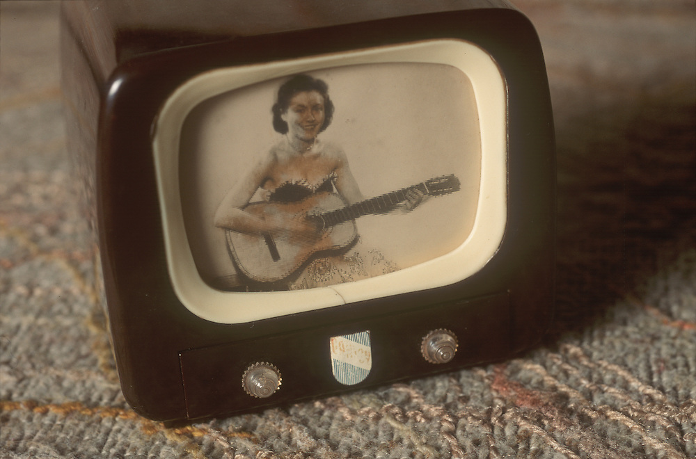 Iconic vintage tiny toy TV showing a woman playing a guitar on the screen. Television was invented in the 1940's or 1950's. The T.V. is made from bakelite. From the collection of Bernard Sampson, Houston, Texas.