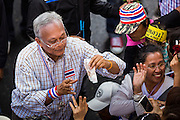 05 JANUARY 2014 - BANGKOK, THAILAND: SUTHEP THAUGSUBAND, leader of the anti-government movement, reaches for cash offered by a supporter during a march through Bangkok Sunday. People handed hundreds of thousands of Thai Baht to Suthep as he led the march. Suthep is a former Deputy Prime Minister and member of the opposition Democrat Party who resigned to organize the protests against the Pheu Thai government.  He led the protestors on a march through the Chinatown district of Bangkok. Tens of thousands of people waving Thai flags and blowing whistles gridlocked what was already one of the most congested parts of the city. The march was intended to be a warm up to their plan by protestors to completely shut down Bangkok starting Jan. 13.     PHOTO BY JACK KURTZ