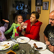 Sydney Ladeau, 10, left, Whitney Ladeau, 7, center left, Angie Ladeau, center right, and Brett Ladeau, right, 44, of Hartland, enjoy a fried turkey dinner after cleaning Sydney's tom from youth opener at their home in Hartland on April 30, 2012.