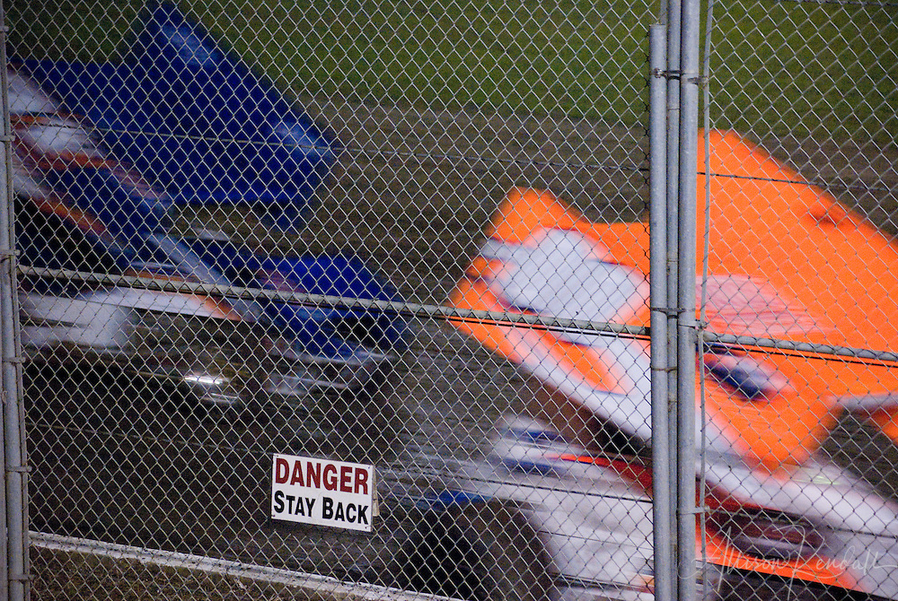 Karts race past chainlink fence on the dirt track at Ocean Speedway in Watsonville California