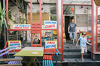 """NAPLES, ITALY - 13 JULY 2017: Customers walks out of """"In Tabula"""", a cafe and lunch restaurant in Piazza Bellini in Naples, Italy, on July 13th 2017."""