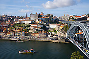 Rabelo port wine barge and The Ponte de Dom Luis I - metal arch bridge over River Douro connecting Porto to V|la Nova de Gaia, Portugal