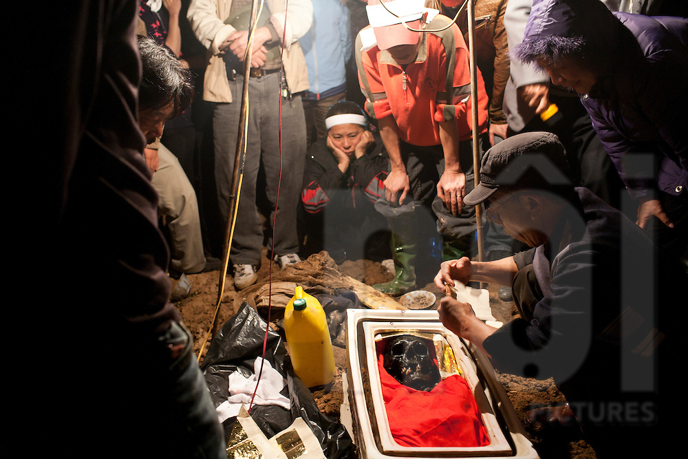 Family watching the traditional exhuming ritual at midnight in which the remains are removed for a second burial in a new plot, Hoai Duc District, Hanoi, Vietnam, Southeast Asia