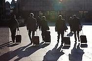 Europe, Germany, North Rhine-Westphalia, Cologne, men with trolleys at the square Roncalliplatz in front of the cathedral. ..Europa, Deutschland, Nordrhein-Westfalen, Koeln, Maenner mit Trolleys gehen ueber den Roncalliplatz am Dom.