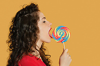 Side view of a young woman licking lollipop over colored background