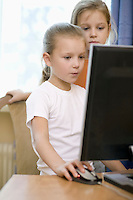 Two girls stand at computer on desk in apartment