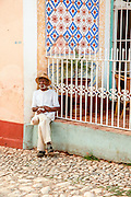 a man with cigar sits in the street. Cuba, Trinidad.