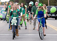 "Seniors Jessie Byran and Stephanie Lund lead their ""Green"" class representing the United Nations Environment Program down the streets of downtown Laconia during the annual Homecoming Parade Friday evening.  (Karen Bobotas/for the Laconia Daily Sun)"