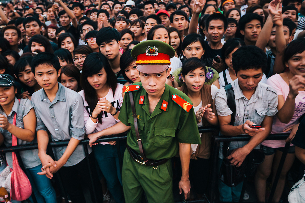 A police officer stands in front of a crowd during a concert in Hanoi, Vietnam.