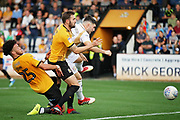 MKDons defender Jordan Moore-Taylor (15) gets in a shot despite the close attention from Cambridge United's Greg Taylor(5) and Cambridge United's Louis John(25) during the EFL Sky Bet League 2 match between Cambridge United and Milton Keynes Dons at the Cambs Glass Stadium, Cambridge, England on 13 October 2018.