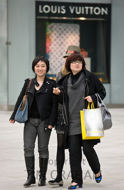 Chinese women pass Louis Vuitton clothes shop, in Nanjing Road designer shopping district, central Shanghai, China