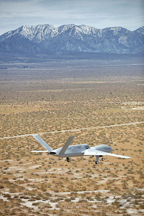 "General Atomics P46 Predator 'C', ""Avenger"" prepares to land at Grey Butte Airfield after its second succesful test flight. The latest generation Predator is a jet-powered remotely-piloted vehicle (RPV) that is nearly twice the size of its predecessor. Featuring an internal weapons bay, retractable gear, a blended wing design, top-mounted intake and shielded exhaust, the stealthy airframe can cruise at 50,000 feet and can perform multiple tasks from reconnaisance to attack roles."