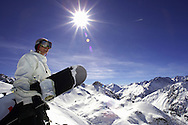Female snowboarder stands on summit of mountain. Serre Chevalier