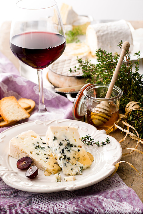 two slices of roquefort blue cheese grape berry and thyme on a dish with honey and red wine glass