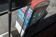Looking down from the top deck of a bus are posters stuck to the back of an old phone kiosk on the Walworth Road in Southwark, on 10th April 2019, in Westminster, London, UK
