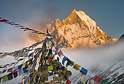 """Machhapuchhre (or Machhapuchhare), the Fish Tail Mountain (22,943 feet / 6997 meters elevation) is a sacred peak, illegal to climb, in the Annapurna mountains (part of the Himalaya range), in Nepal. Tibetan Buddhist prayer flags fly from a monument at Annapurna South Base Camp (ABC, at 13,550 feet elevation) in the Annapurna Sanctuary. Published in Wilderness Travel 2016 Catalog of Adventures and as double page spread inside the cover of Wilderness Travel 2009 Catalog of Adventures, and in 2009 on Swedish travel outfitter web site www.adventurelovers.se. Published in """"Light Travel: Photography on the Go"""" book by Tom Dempsey 2009, 2010."""