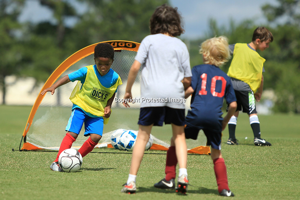 Jace Gray, 6, of Tupelo, puts a move on two defenders as he makes his way to the goal to score during a two on two scrimmage at the Tupelo Youth Soccer Association's Soccer Camp at Ballard Park in Tupelo.
