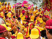 "23 JUNE 2015 - MAHACHAI, SAMUT SAKHON, THAILAND: Men carry the City Pillar Shrine away from a boat on the Tha Chin (Chin River) during the procession for the shrine in Mahachai. The Chaopho Lak Mueang Procession (City Pillar Shrine Procession) is a religious festival that takes place in June in front of city hall in Mahachai. The ""Chaopho Lak Mueang"" is  placed on a fishing boat and taken across the Tha Chin River from Talat Maha Chai to Tha Chalom in the area of Wat Suwannaram and then paraded through the community before returning to the temple in Mahachai.   PHOTO BY JACK KURTZ"