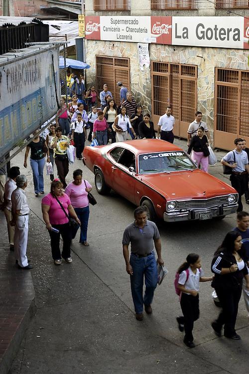 Pedestrians on their way to work in Petare, a poor hillside slum in eastern Caracas