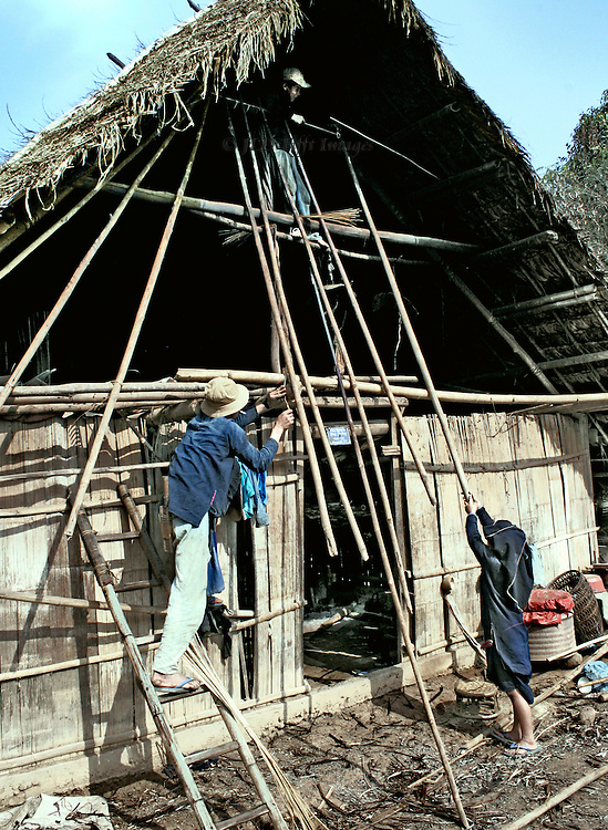 New house building in a Laotian village.  Man on a ladder, woman on the ground, boy up under the roof, all wielding stakes into place to hold up the roof.  A do-it-yourself project for the whole family.