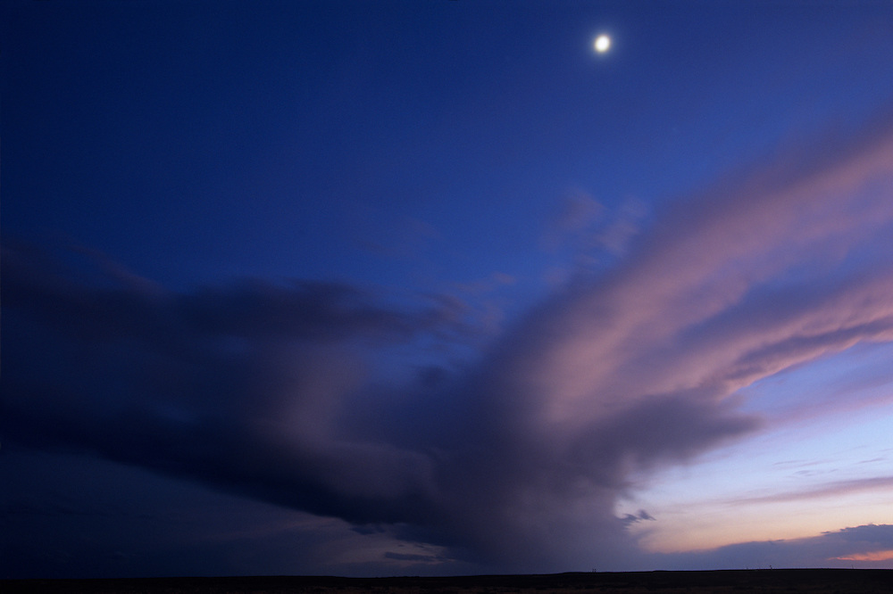 USA, New Mexico, Fort Sumner, Crescent moon hangs above blurred storm clouds on high desert plateau at dusk