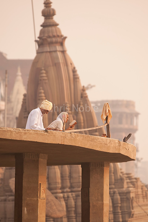 Worshipers greet the dawn at Scindia Ghat, on the banks of the Ganges River, Varanasi India.