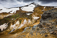 Kerlingarfjöll geothermal area, Highlands of Iceland. Lava boulders in forground and steam from geothermal vents and mudpools in background.