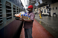 Food vendors sell an array of Indian and imported snacks, through the grilled windows of the sleeper class coach to train passengers of the Himsagar Express 6318 as it stops for 5 minutes at Coimbatore Junction stn. at the border of Tamil Nadu on 9th July 2009.. .6318 / Himsagar Express, India's longest single train journey, spanning 3720 kms, going from the mountains (Hima) to the seas (Sagar), from Jammu and Kashmir state of the Indian Himalayas to Kanyakumari, which is the southern most tip of India...Photo by Suzanne Lee / for The National
