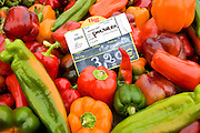 Local produce red peppers, green pepper and yellow pepper on sale at farmers market in Normandy, France