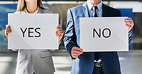 Business people standing while holding white YES or NO placard