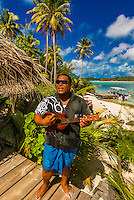 Polynesian man playing a ukelele, Haapiti Motu (a small private island) off Bora Bora, Society Islands, French Polynesia.