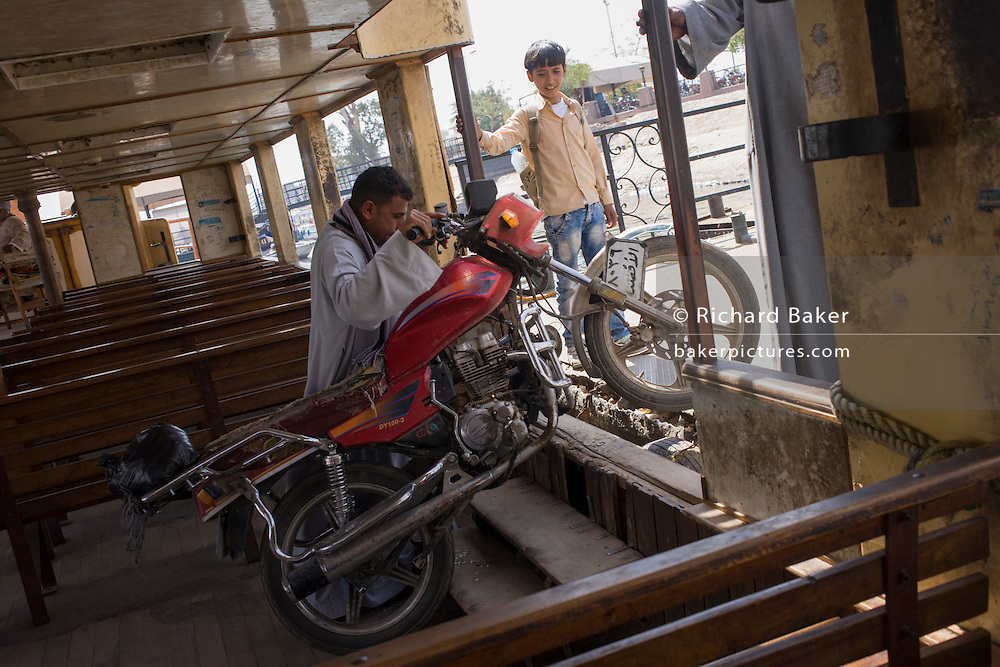 A motorbike is heaved off the state-run ferry across the River Nile at Luxor, Nile Valley, Egypt.