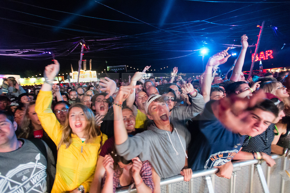 © Licensed to London News Pictures. 27/06/2015. Pilton, UK.  Night-time festival atmosphere at Glastonbury Festival 2015 in the Shangri-La area of the festival on Saturday Day 4 of the festival - festival goers watch the punk band Slaves perform.  Shangri-La is a destroyed dystopian pleasure city.  This years headline acts include Kanye West, The Who and Florence and the Machine, the latter being upgraded in the bill to replace original headline act Foo Fighters. Photo credit: Richard Isaac/LNP