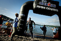 JEROME A. POLLOS/Press..Bryan Rhodes, from Taupo, New Zealand, removes his wetsuit as he races to the transition area as the first one to exit the water following the 2.4-mile swim Sunday during the Ford Ironman Coeur d'Alene.